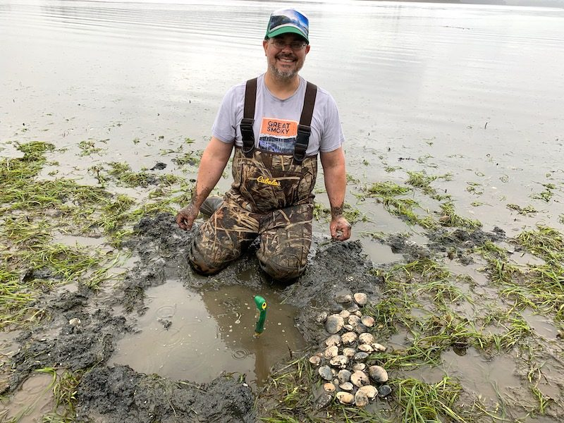 Scientist in rubber waders kneeling in shallow water with a lot of grass in it.