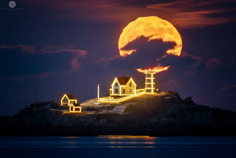 Big full moon, lighthouse, and keeper's houses outlined with yellow holiday lights.