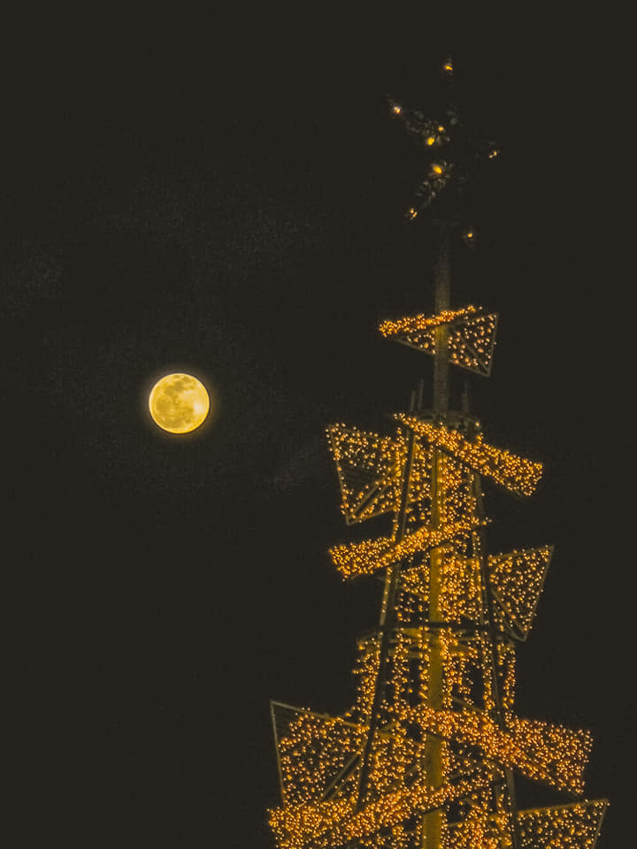Yellow round moon in a dark sky. On right radio tower with all antennas decked out in lights.