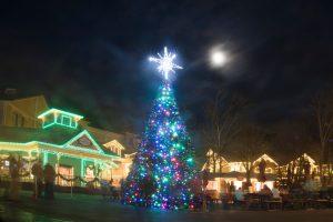 Night scene: Christmas lights on houses, big outdoor Christmas tree, moon overhead.