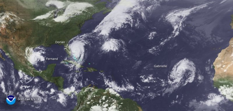 Satellite view of several spiral storms in white on deep blue Atlantic ocean.