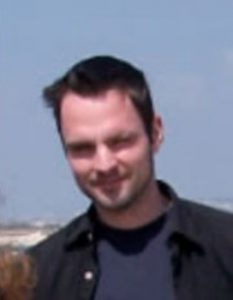 Somewhat blurry photo of a squinting astronomer under a daytime sky.