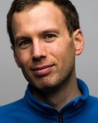 Man with blue shirt in front of gray background.