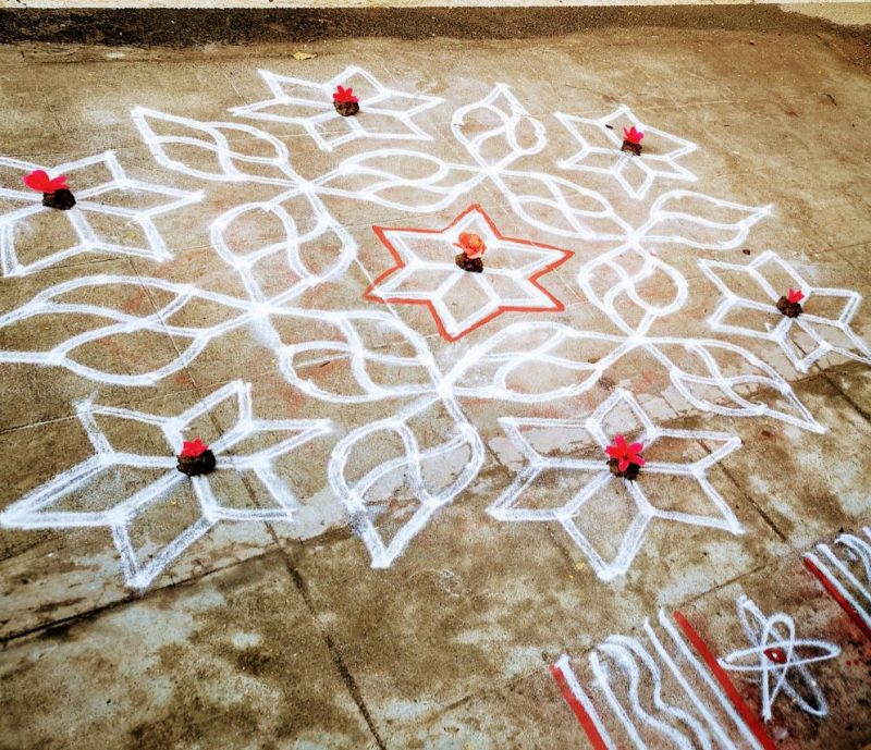 Geometric shape with white swirls and six-point figures drawn on the ground.