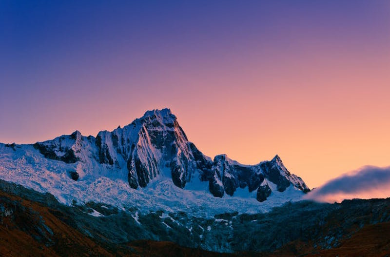 Majestic snowy, rocky, steep mountaintop against a twilight sky fading from pink to blue.