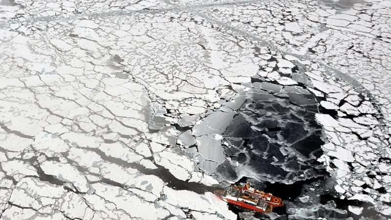 Vast area of ice-covered water, and two small red ships.