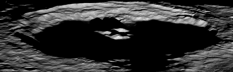 Oblique view of wide crater, floor very black, rim and three small central hills showing white.