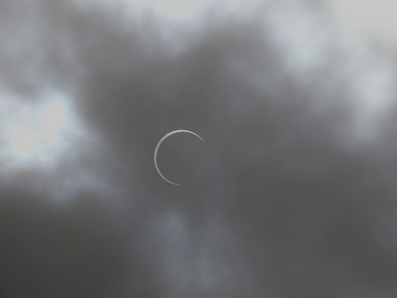 Very thin partial crescent sun among fluffy gray clouds.