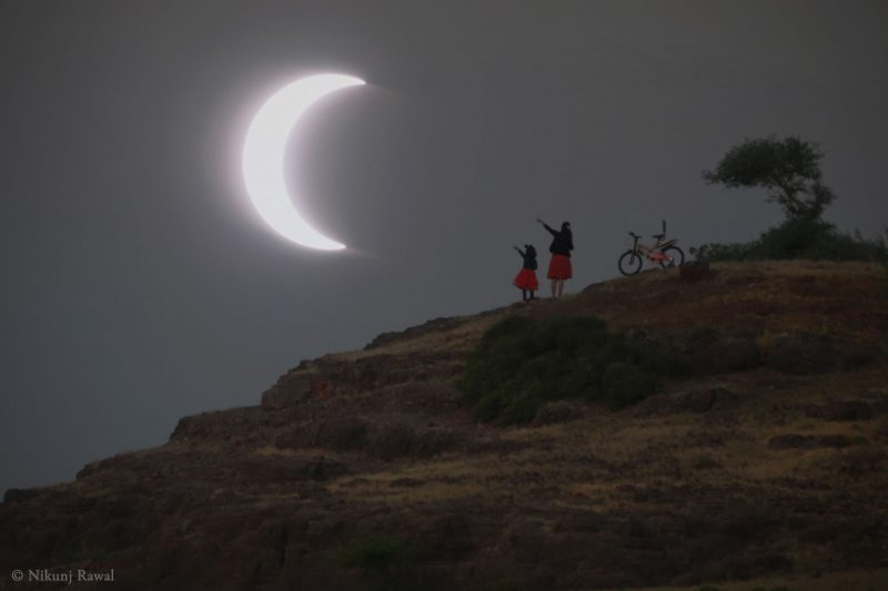 Thin partial eclipse with a woman and child standing on a hillside, pointing at it.