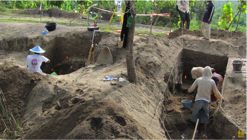 An excavation site, with several large holes in which men are digging.