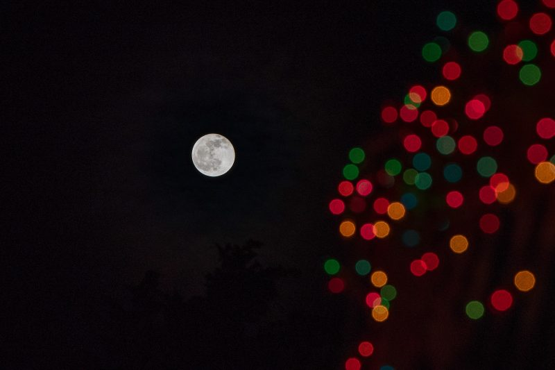 Full white moon floating in black sky; big red, orange, and green dots on the right side of the image.