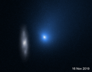 A bluish comet near a distant galaxy.