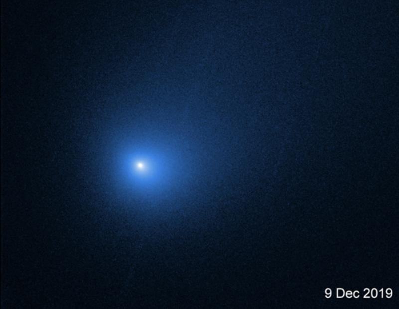 White dot surrounded by slightly elongated large blue hazy area.