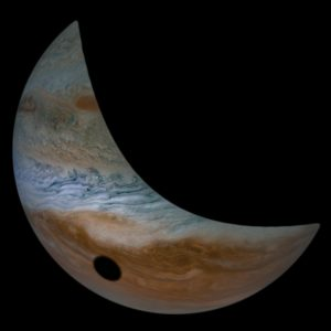 A crescent Jupiter, with Io's black shadow on its cloudtops.