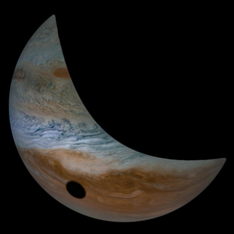 A crescent Jupiter, with Io's oval black shadow on its cloudtops.
