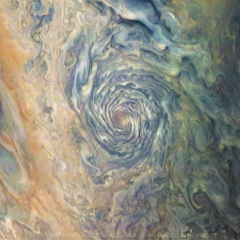 A swirling blue and white hurricane-like vortex on Jupiter.