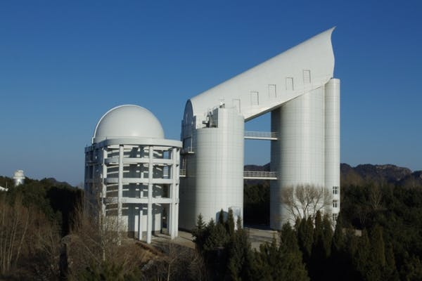 Dome observatory on left, building-sized angled telescope housing at right.