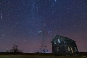 A long meteor beside a night scene of a radio tower and large house or barn.