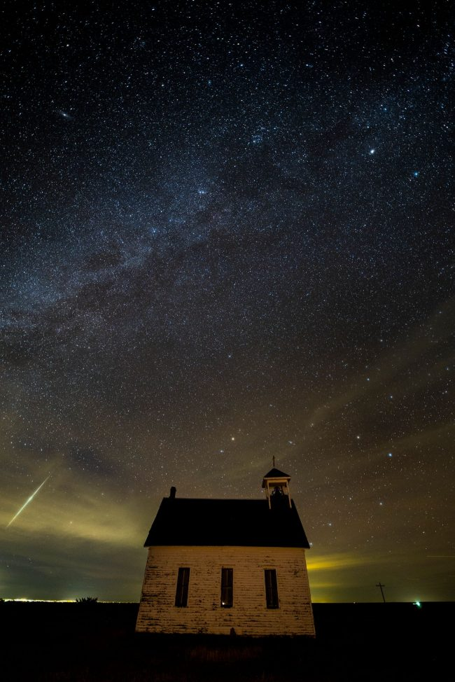 Small, old church in isolated location, dark sky, with a bright meteor streaking through the scene.
