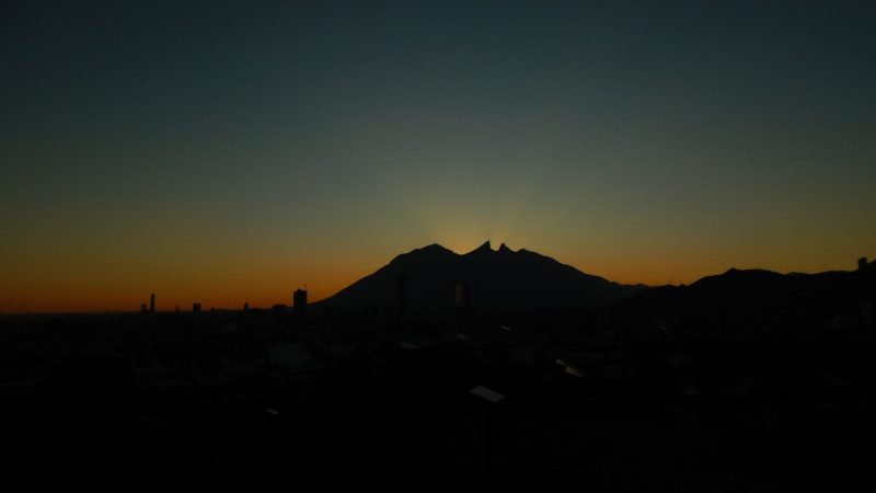 silhouette of 2 peaks with orange light behind them.