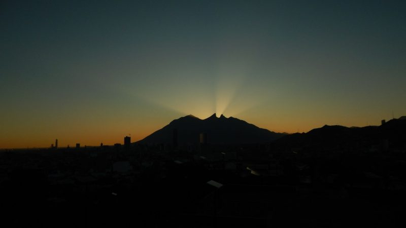 silhouette of 2 peaks with orange light behind them and sun rays between them.