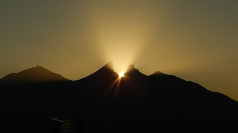 Mountain with yellow-orange light emanating between 2 peaks and sun visible between them.