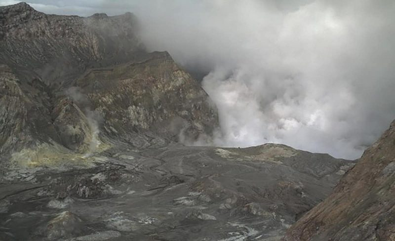Gray rocks sloping down into crater and smoke.
