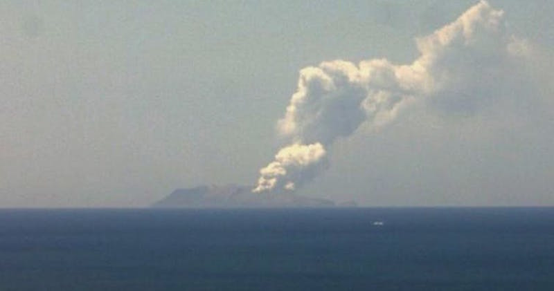 Distant island, with plume of smoke rising into the sky over the ocean.