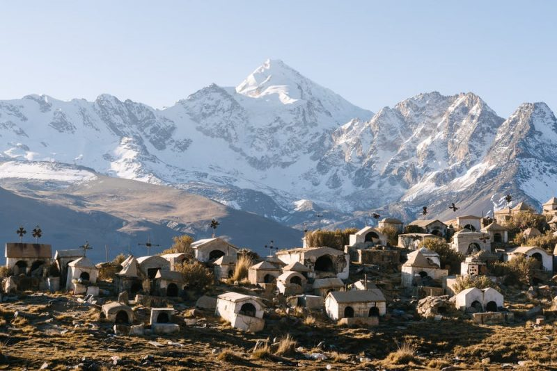 Many small white stone houses or possibly tombs in front of snow-covered mountain.
