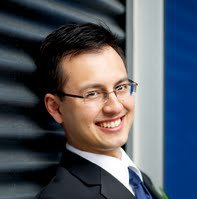 Smiling man in suit leaning against wall.