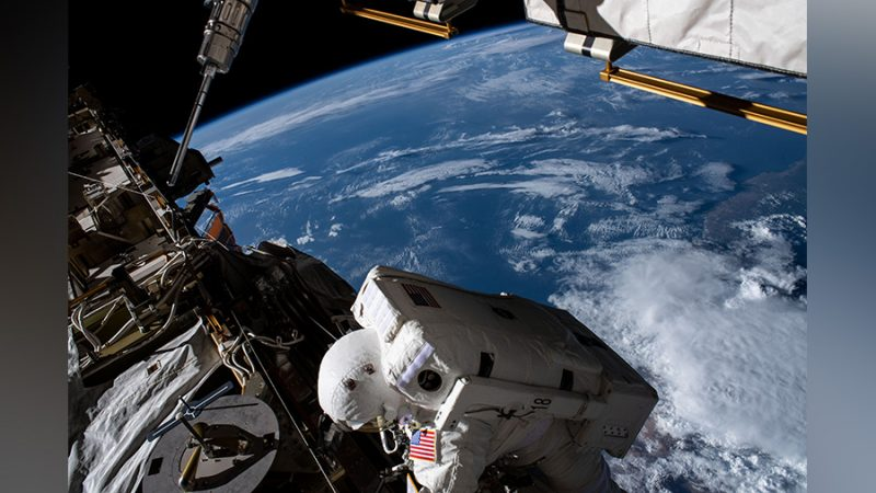 Astronaut in white spacesuit with big rectangular backpack outside the ISS, Earth in the background.
