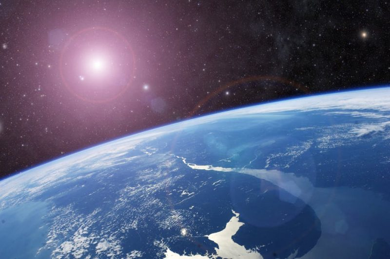 Earth seen from space with sun and stars in background.