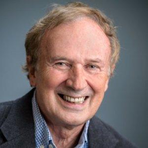 Smiling man with dark background.