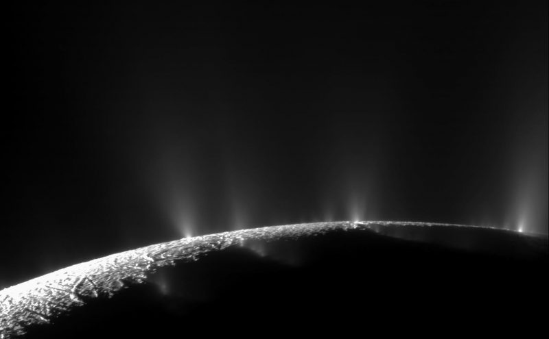 Dark, wrinkled surface of a moon with bright geysers on horizon.