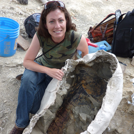 Woman holding large fossil.