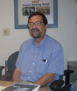 Man in blue shirt with beard and glasses.