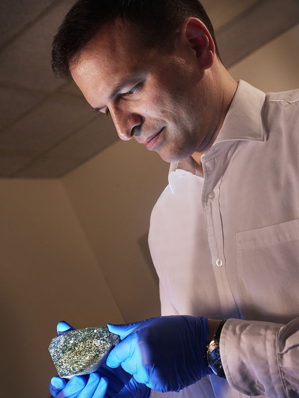 Man with blue latex gloves holding a granular rock.