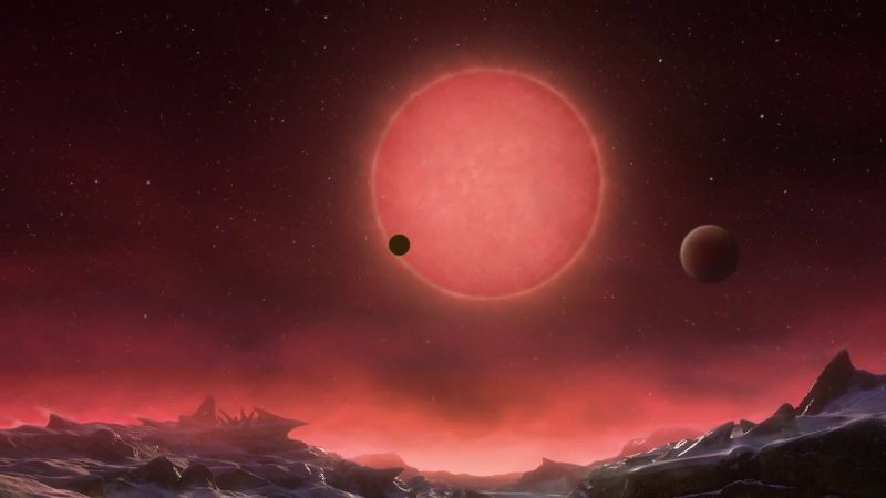 Icy landscape with red star and planets in sky.