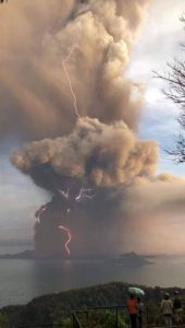 Cloud of volcanic ash spewing high into the air, with lightning in the cloud.