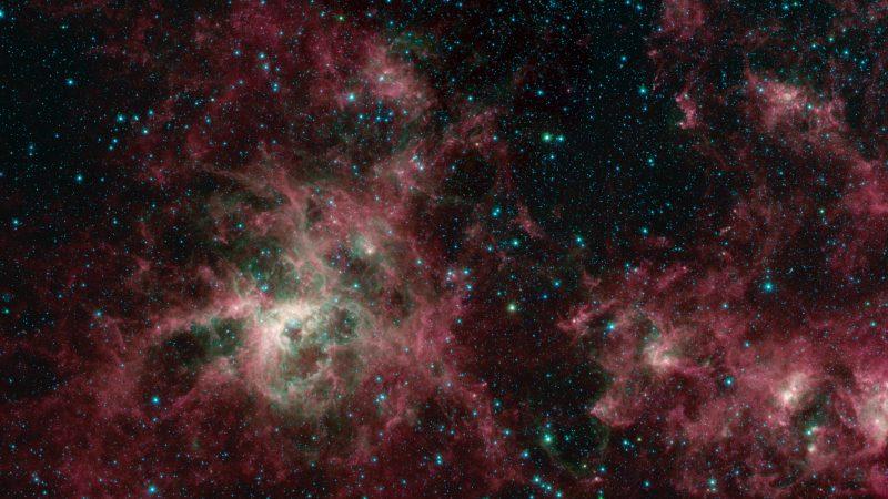 Colorful wispy nebula with starry background.