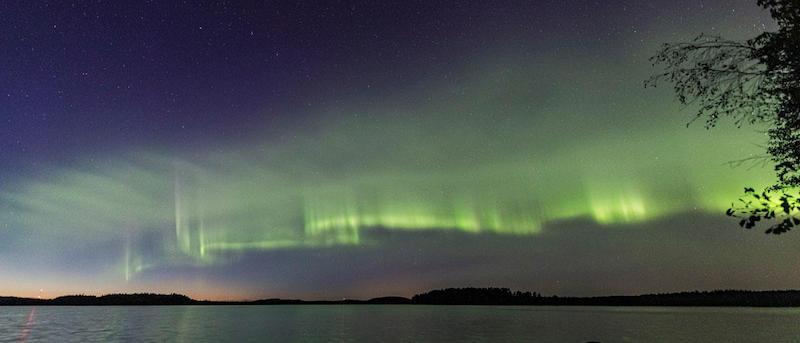 Horizontal waves of green light above a seacoast.