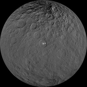 A round world with many craters. In one crater, there are 2 very bright spots.