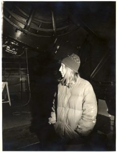 A girl in a puffy jacket and sock hat, standing next to the base of a large telescope.