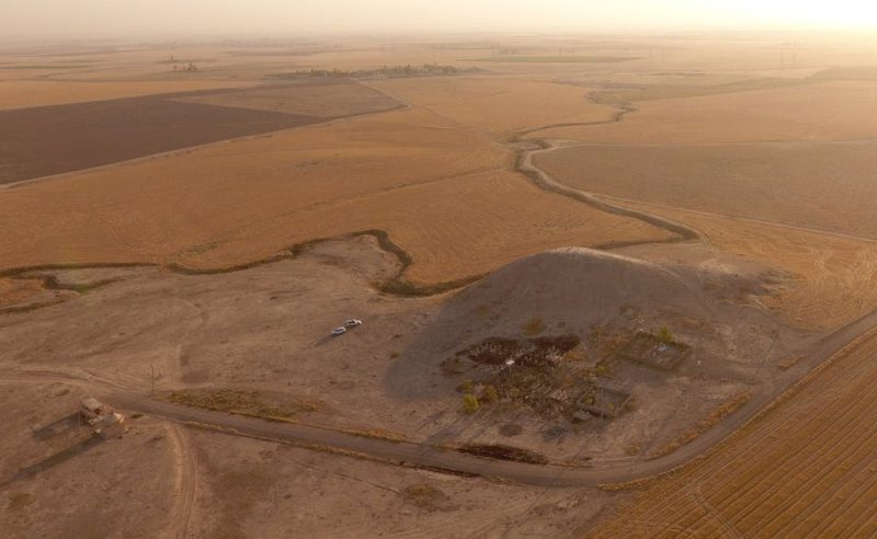 Aerial view of barren, brown landscape with a road and small hill.