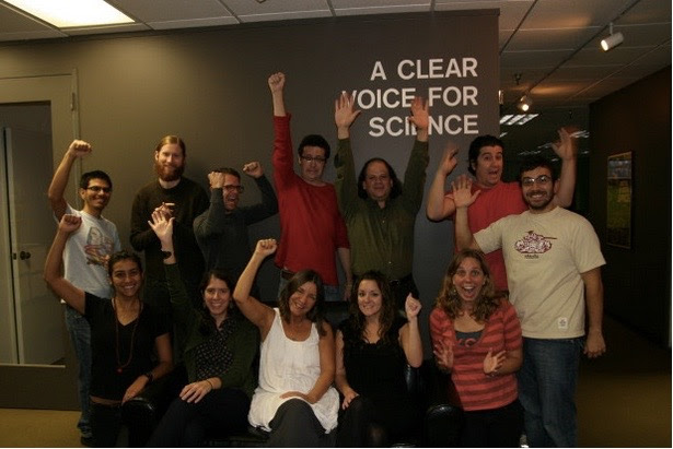 A group of jubilant people, sitting and standing under a sign that says 'A Clear Voice for Science'.