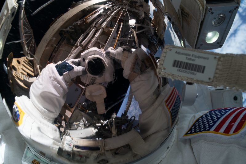 Reflection of camera in shiny, spherical visor of helmet of astronaut.