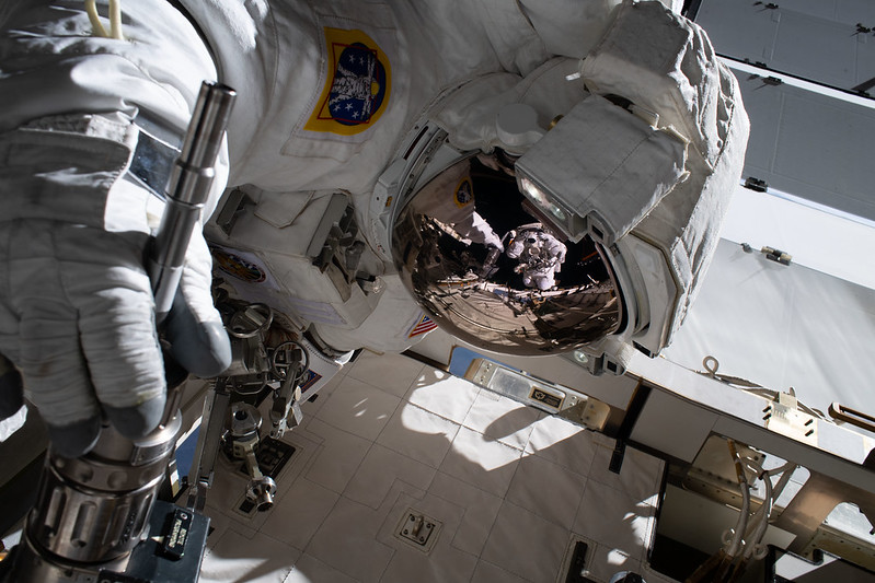 Space-suited astronaut outside ISS with reflection of another astronaut in shiny helmet visor.