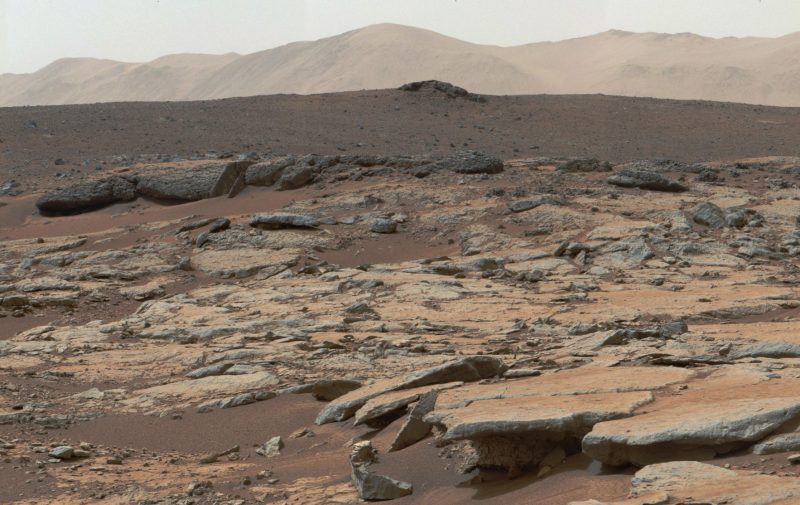 Rocky and sandy terrain with mountains in background.