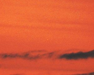 A very orange sky after sunset; Mercury can barely be seen behind the glare.