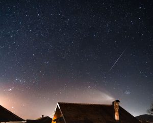 A bright meteor streak past the roof of a house.